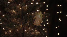 Female hanging fairy decoration on Christmas tree on bokeh lights background.  stock footage