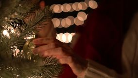 Female hanging gold Christmas ball on tree with bokeh lights background.  stock footage