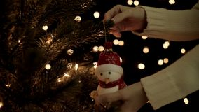 Female hanging snowman decoration on christmas tree on bokeh lights background.  stock footage