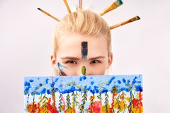 Female has artistic makeup in the form of strokes acrylic paint. Creative girl looks out of picture, you can see only eyes royalty free stock images