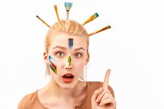 Female has artistic makeup in the form of strokes acrylic paint. Stylish Bob hairstyle with stuck brushes in blond hair. stock photo