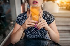 Female has lunch with cold lemonade cocktail,. Woman has breakfast in morning and drinks fresh orange juice Royalty Free Stock Images
