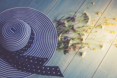 Female hat, striped, bouquet of wildflowers, top view. On a wooden background. Blue color. Conceptual image. Stock Photo