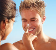 Female having fun by applying cream on man's nose Royalty Free Stock Images