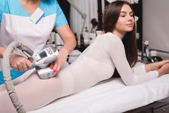 Female having procedure of massage on legs in apparatus cosmetology clinic. Woman in special white suit getting anti stock images