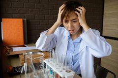 Female headache scientist at lab. Asian female headache scientist at lap covering her head with hands when seeing many chemical liquid in pipes and not know what Stock Image