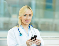 Female health care professional, doctor holding smart phone Royalty Free Stock Photo