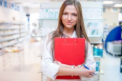 Female health care worker smiling in pharmacy Stock Images