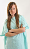 Female healthcare patient - hospital gown. Attractive brunette Caucasian patient wearing a blue green hospital gown - unhappy or angry - scowl Royalty Free Stock Photos