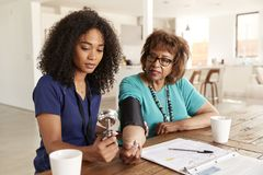 Female healthcare worker checking the blood pressure of a senior woman during a home visit