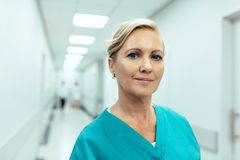 Female healthcare worker standing in hospital corridor. Close up portrait of female healthcare worker standing in hospital corridor. Caucasian woman in hospital Royalty Free Stock Photo