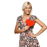 Female with heart shape. Young blond female in summer dress holding red heart shape near her heart isolated on white background royalty free stock images
