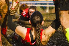 Female helped by a helping hand on a extreme mud racer. Mud race runners assistance stock photos
