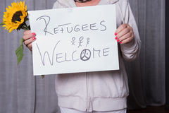 Female helper welcomes refugees with sunflower.  royalty free stock images