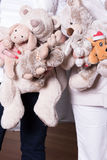 Female helpers offer toys to refugee children.  stock photo