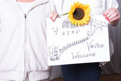 Female helpers welcome refugees with sign.  stock image