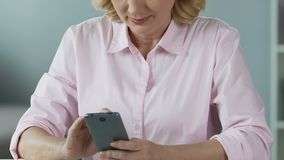Female in her 50s scrolling news in social networks on smartphone, close-up. Stock footage stock footage