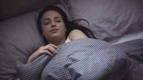 Female in her 20s wakes up in the morning in a bed, girl is stretching herself after sleeping. stock video footage
