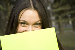 Female hiding behind a folder Stock Photos