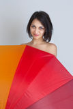 Female hiding over colorful umbrella Stock Photography