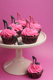 Female high heel stiletto shoes decorated pink and black red velvet cupcakes - vertical. Stock Photos