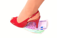 Female high-heeled shoe presses money. On white background Royalty Free Stock Photo