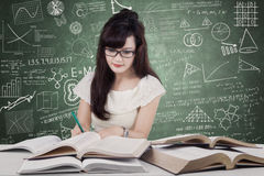 Female high school student learns in class. Photo of a pretty female high school student learning in the class while writing and reading books Royalty Free Stock Photos