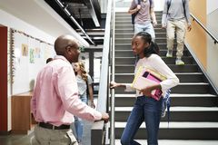 Female High School Student Talking With Teacher In Busy Corridor royalty free stock photography