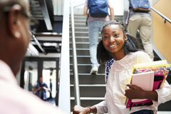 Female High School Student Talking With Teacher In Busy Corridor royalty free stock images
