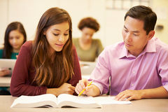 Female High School Student With Teacher Studying At Desk Stock Photography