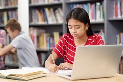 Female High School Student Working At Laptop In Library. Female High School Student Works At Laptop In Library Royalty Free Stock Photos