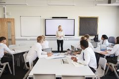 Free Female High School Teacher Standing Next To Interactive Whiteboard And Teaching Lesson To Pupils Wearing Uniform Stock Image - 134206821