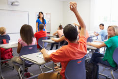 Female High School Teacher Taking Class. With Male Pupil Raising Arm To Answer Question royalty free stock photos