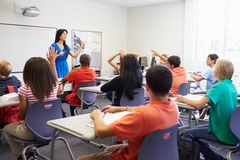 Female High School Teacher Taking Class. With Students Raising Their Hands Stock Photos