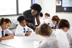 Female High School Tutor Helping Students Wearing Uniform Seated Around Tables In Lesson royalty free stock photo