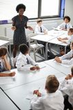 Female High School Tutor Helping Students Wearing Uniform Seated Around Tables In Lesson royalty free stock image