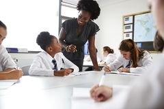 Female High School Tutor Helping Students Wearing Uniform Seated Around Tables In Lesson stock image
