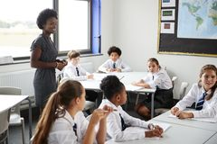 Female High School Tutor Helping Students Wearing Uniform Seated Around Tables In Lesson stock photos