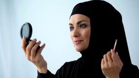 Female in hijab applying lipstick holding hand mirror, femininity and beauty. Stock photo stock photography