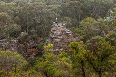 Adventurous female hiker climbed up onto rocky tower in mountain bushland stock photos