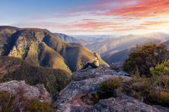 Female hiker admiring mountain wilderness beauty. Female bushwalker sitting on cliff ledge admiring mountain beauty as sunrise light hits the sides of the stock images