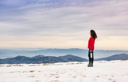 Female hiker admiring winter scenery on a mountaintop. Alone Royalty Free Stock Photography