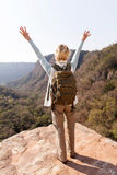 Female hiker arms open. Back view of female hiker arms open on mountain cliff Stock Image