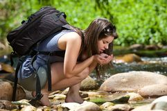 Female hiker with backpack drinking water from stream in nature Stock Images