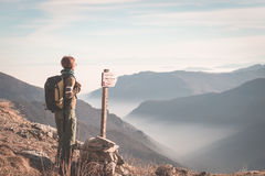 Female hiker with backpack looking at the majestic view on the italian Alps. Mist and fog in the valley below, snowcapped mountain. Peak in the background Stock Photos