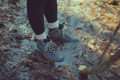 Female hiker with boots in leafy puddle Stock Photography
