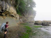 A female hiker carefully navigating the coast line along the West Coast Trail stock photography