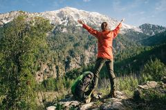 Female hiker celebrating view of Tahtali in Turkey. Backpacker with her hands raised standing next to her backpack celebrating view of Tahtali on a sunny day Stock Image