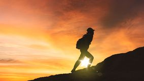 Female hiker climbing a hill at sunset time stock photography