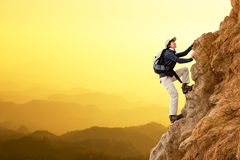 Female hiker climbing rocks. Royalty Free Stock Photography